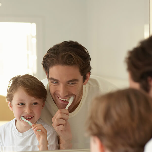 A dad brushing his teeth next to his little son while they are reflected in the mirror