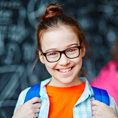 A girl with glasses smiling in front while standing with a blue backpack