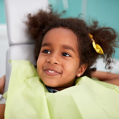 A little girl sitting in a chair at our pediatric dentist in East Norriton PA and wearing a dental bib