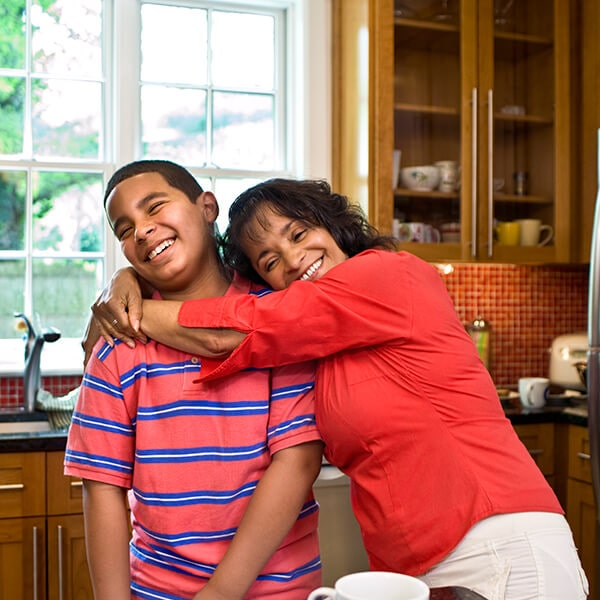 A mom hugging her son in the kitchen while they are sitting and getting ready to visit Farm Park Pediatric Dentistry