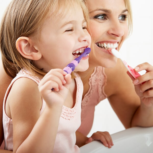 A mother brushing her teeth with her little daughter while they smile and look in the mirror