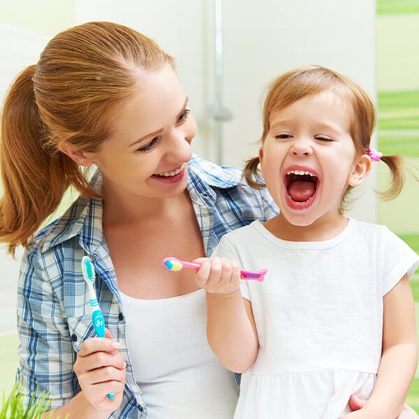 A young mom teaching her little daughter how to brush her teeth before visiting Farm Park Pediatric Dentistry
