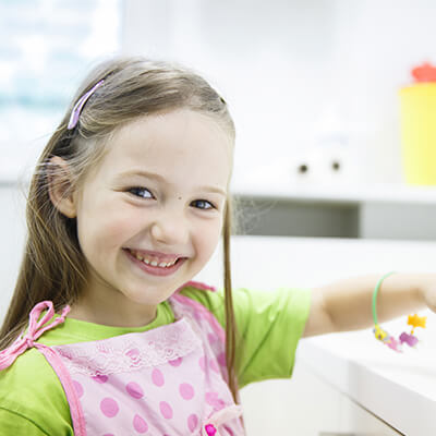 A girl in the kitchen wearing a pink apron while smiling