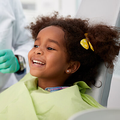 A girl getting services in the dentist's chair while smiling and wearing a green bib