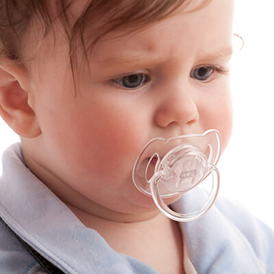 A little boy wearing a pacifier while looking down