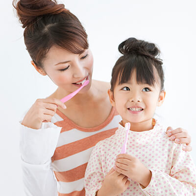 A mother teaching her little daughter how to brush her teeth